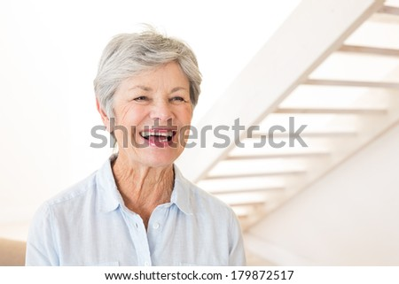 Retired woman smiling and laughing at home in living room - stock photo