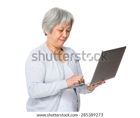 Retired woman use of laptop computer - stock photo