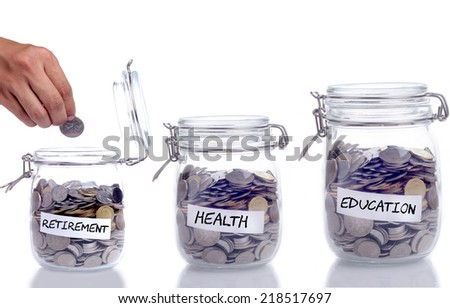 Retirement, Health and Education concept: Glass jar with coin and hand putting the coin into the jar - stock photo