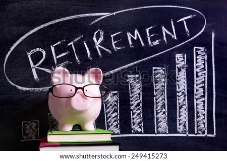 Retirement plan : Pink piggy bank with glasses standing on books next to a blackboard with retirement plan savings message.  Pension fund growth. - stock photo