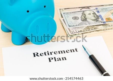 Retirement plan with banknote, piggy bank, and pen - stock photo