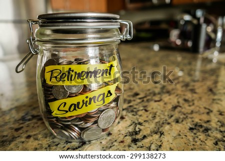 "Retirement Savings Money Jar. A clear glass jar filed with coins and bills, saving money. The words ""Retirement Savings"" written on the outside. - stock photo"