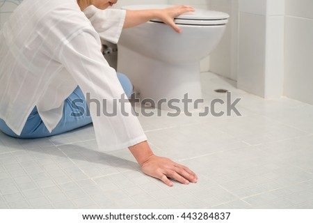 Retirement woman fell down in a restroom - stock photo