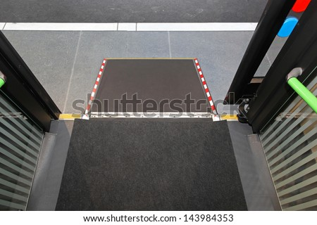 Retractable ramp for wheelchair at city bus - stock photo