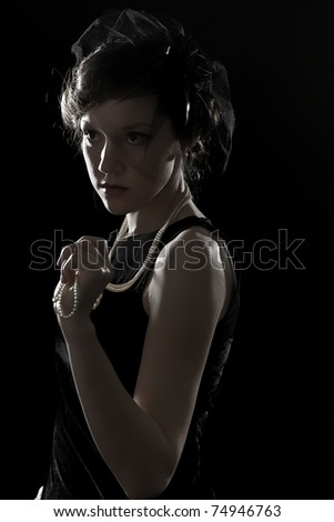 Retro a portrait of the beautiful brunette against a dark background - stock photo