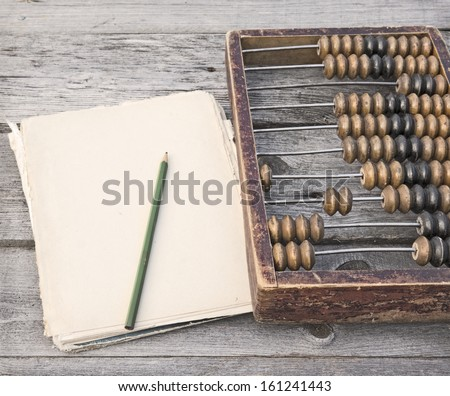 Retro abacus, pencil and paper on a wooden table - stock photo