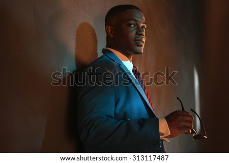 Retro african american businessman in blue suit holding sunglasses. Leaning against gray wall. - stock photo
