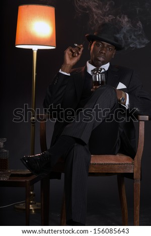 Retro african american gangster man wearing striped suit and tie and black hat. Sitting in a chair in living room. Smoking cigar. Holding glass of whisky. - stock photo