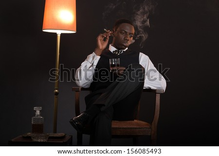 Retro african american gangster man wearing striped suit and tie. Sitting in a chair in living room. Smoking cigar. Holding glass of whisky. - stock photo