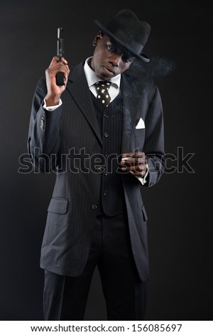 Retro african american mafia man wearing striped suit and tie and black hat. Holding a gun. Smoking cigarette. Studio shot. - stock photo