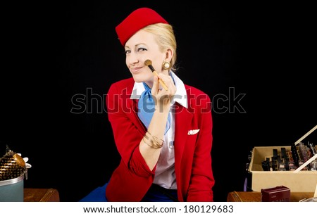 Retro Airline Stewardess or Flight Attendant Applying Make-up with a Brush at her Vanity - stock photo