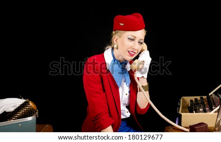 Retro Airline Stewardess or Flight Attendant talking on the Phone While Preparing for Work. - stock photo