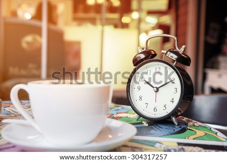 retro alarm clock and Cappuccino cup with blur coffee shop background, warm tone  - stock photo