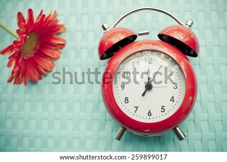 Retro alarm clock and gerbera flower on blue texture background. - stock photo
