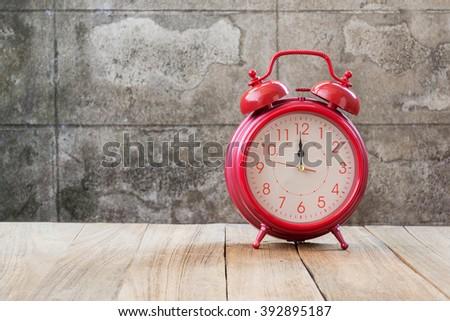 retro alarm clock (12 o'clock)on wood table - stock photo