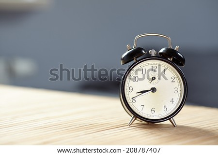 Retro alarm clock on desk front grey wall background  - stock photo
