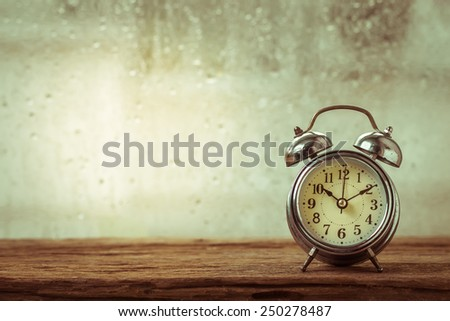 retro alarm clock on table in front the rain - stock photo