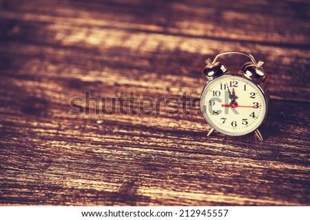 Retro alarm clock on wooden background - stock photo