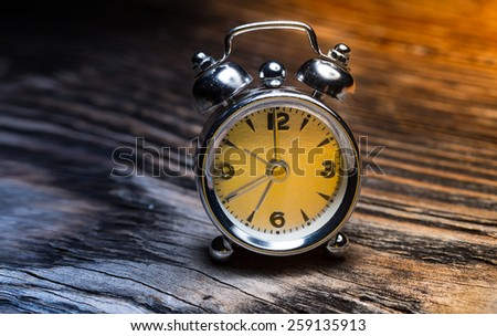 Retro alarm clock on wooden table. Blue and Yellow. Sunrise Concept - stock photo