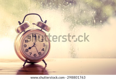 retro alarm clock on wooden table on  rainy day window background  in vintage color tone - stock photo