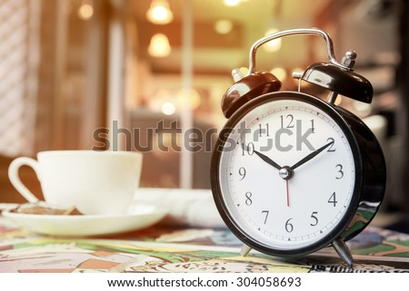 Retro alarm clock with cup of cappuccino and newspaper in coffee shop, coffee break time, warm tone - stock photo