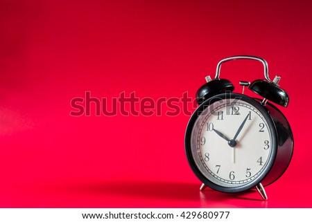 Retro alarm clock with five minutes past ten o'clock,Retro Clock with red background. Clock concept.  - stock photo