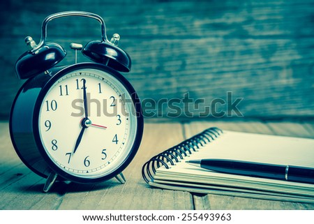 retro alarm clock with notebook and pen - stock photo
