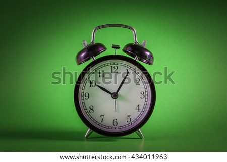 Retro alarm clock with Ten o'clock and five minute on green background with Vignetting effect.clock concept. - stock photo
