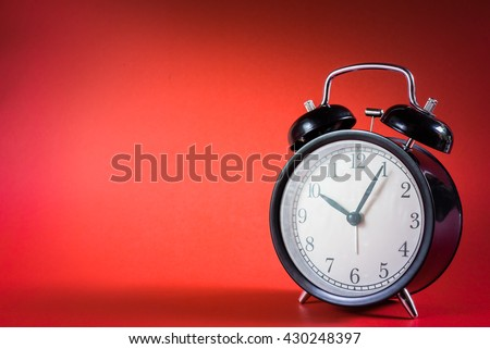 Retro alarm clock with Ten o'clock and five minute on red background . - stock photo