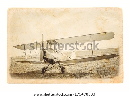 Retro aviation concept - travel landscape with biplane. Old airplane at the airfield. Retro image of the old aircraft on paper texture. Vintage background with airplane of the grunge style. - stock photo