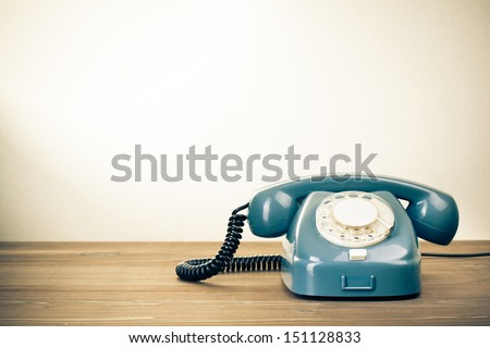 Retro background with rotary telephone on wood table - stock photo
