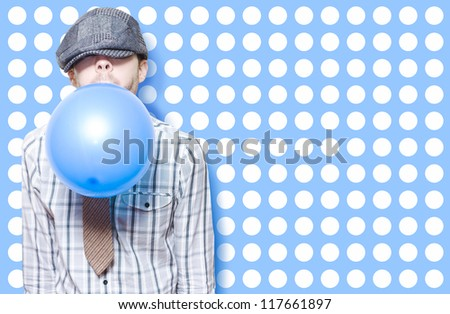 Retro Birthday Kid Blowing Up A Blue Party Balloon On Cute Polka Dot Card Background - stock photo