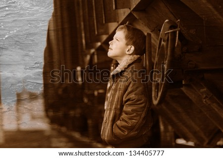 Retro black and white photo of sepia boy bum blonde in brown jacket and crumpled jeans on street near car look up - stock photo