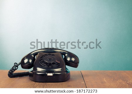 Retro black telephone on table front mint green background - stock photo
