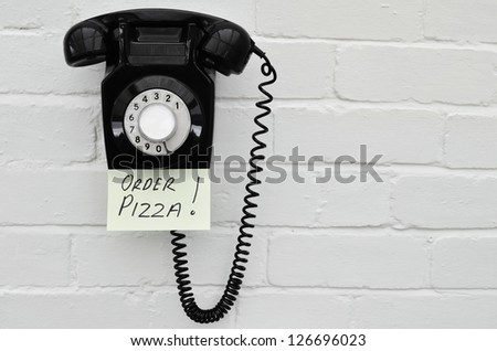 Retro black telephone with a reminder note to order pizza - stock photo
