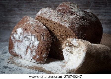 retro bread in rustic style background.Fresh traditional bread on wooden ground with flour in a sack.  - stock photo