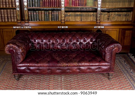 Retro brown leather couch in reading room - stock photo