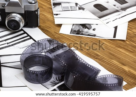 retro camera and some old photos on wooden table - stock photo