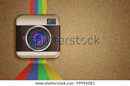 retro camera icon with rainbow colors on cork board background - stock photo