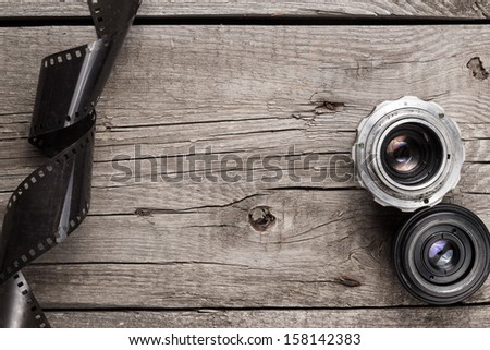 retro camera lenses and negative film on wooden table - stock photo