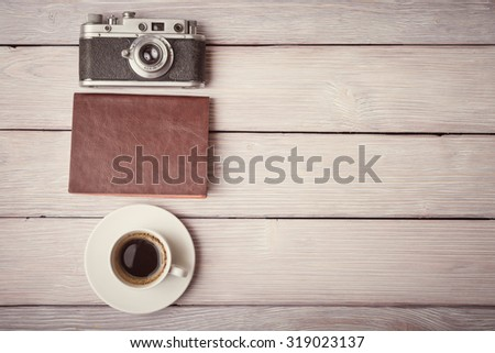 Retro camera, notebook and cup of coffee on wooden desk - stock photo