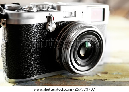 Retro camera on old wooden table background - stock photo