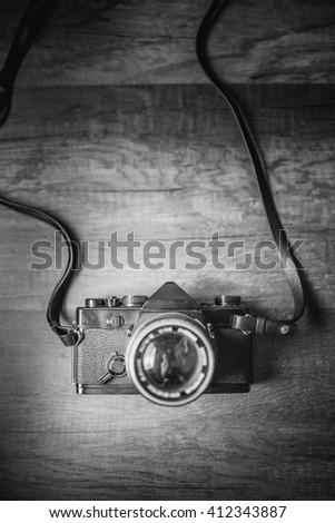 Retro camera on wood table background , black and white - stock photo