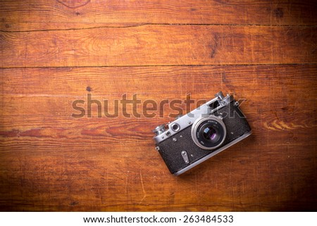 Retro camera on wood table background, vintage color tone - stock photo