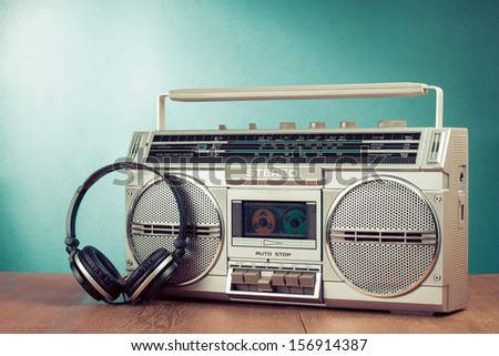 Retro cassette ghetto blaster and phones on table in front mint green background - stock photo