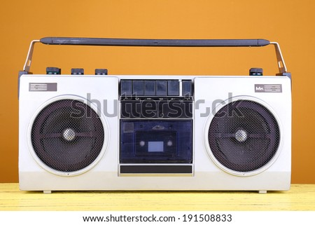 Retro cassette stereo recorder on table on yellow background - stock photo