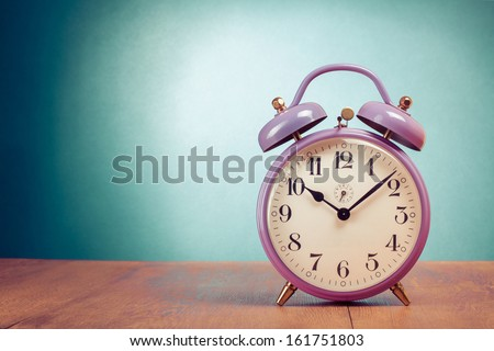 Retro clock on table front gradient mint green background - stock photo