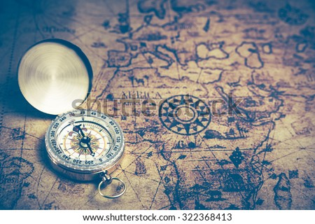 Retro compass on ancient world map, dark vintage style - stock photo