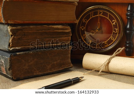 Retro composition with books, clock, paper and pen on wooden background  - stock photo