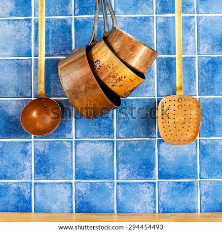 Retro copper utensils. cookware, kitchenware set. Pots, kitchen spoon, skimmer hanging on. Blue tile wall, wood background. - stock photo